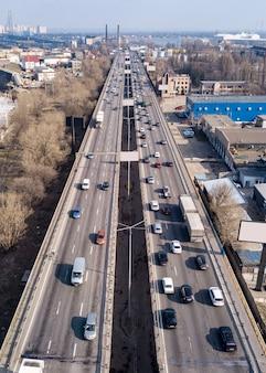 Vista aerea dal cavalcavia di traffico di droni con auto in movimento e camion su una strada asfaltata in una soleggiata giornata di primavera.