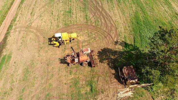 Vista aerea dal fuco di due mietitrebbiatrici e mietitrebbie agricole, stare su un ampio campo marrone tra l'albero verde solitario