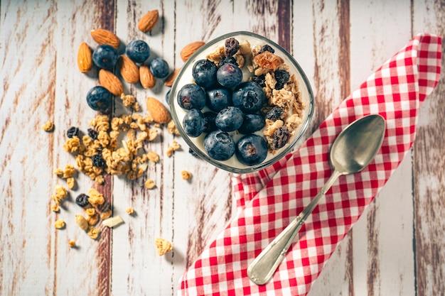 Vista aerea di un bicchiere con parfait di yogurt, mirtilli e muesli su un tavolo in legno rustico. concetto di alimentazione sana e naturale.