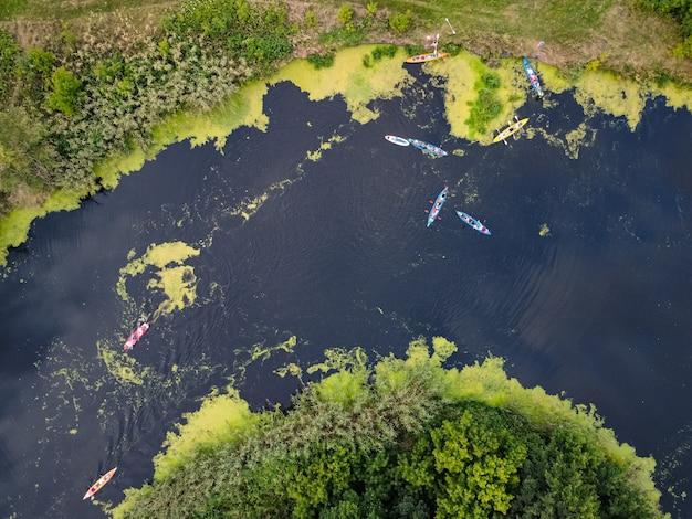 Vista aerea di un gruppo di kayak che viaggiano su un fiume della foresta in una giornata estiva