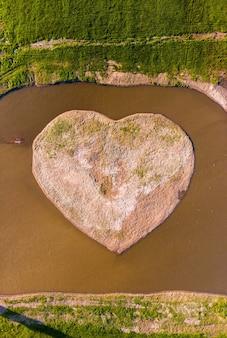 Vista aerea dell'isola a forma di cuore vicino al villaggio di pescatori. una bellissima isola a forma di cuore è bella da vedere sull'isola. l'acqua del lago intorno all'isola.