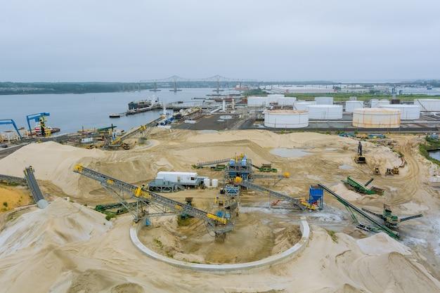 Macchina da costruzione pesante vista aerea che fa costruzione con cantiere di un enorme serbatoio di stoccaggio dell'olio