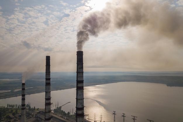Vista aerea di alti tubi del camino con fumo grigio dalla centrale elettrica del carbone. produzione di elettricità con combustibili fossili.