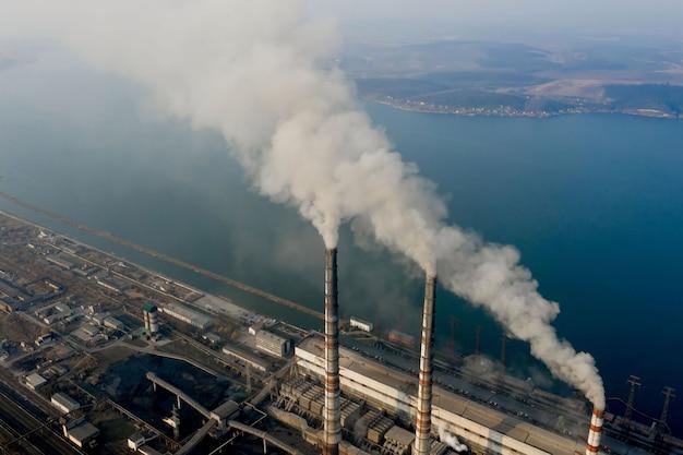 Vista aerea di alte canne fumarie con fumo grigio dalla centrale elettrica a carbone. produzione di energia elettrica con combustibili fossili.