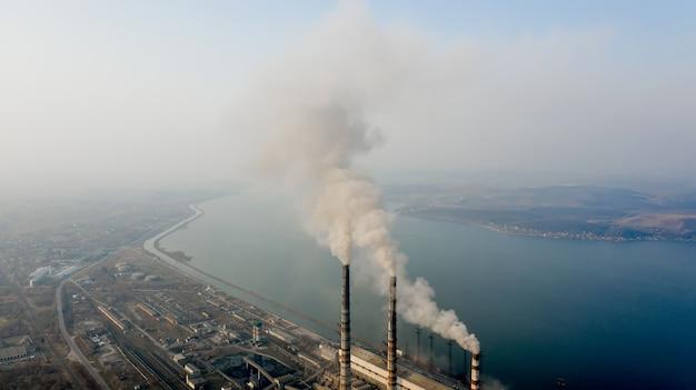 Vista aerea di alte canne fumarie con fumo grigio dalla centrale elettrica a carbone.