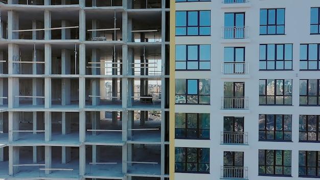 Vista aerea di alto condominio residenziale in costruzione. molte finestre sulla nuova facciata del condominio in costruzione. sviluppo immobiliare.