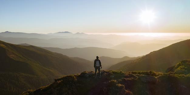 Vista aerea dell'uomo escursionista con lo zaino che si rilassa in cima a una montagna e si gode la vista della valle