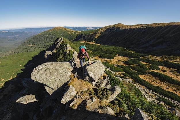 Vista aerea della donna escursionista che si arrampica in cima a un concetto di montagna di turismo e viaggi