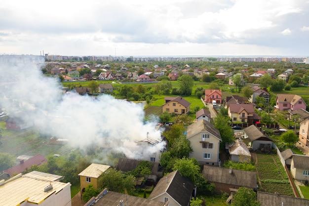 Vista aerea di una casa in fiamme con fiamme arancioni e fumo denso bianco.
