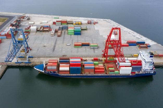 Vista aerea di una nave da carico industriale con contenitori per il carico in un porto marittimo