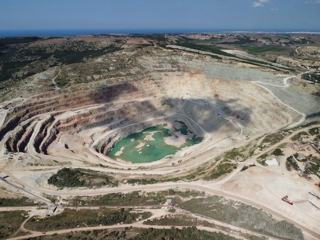 Vista aerea industriale della cava mineraria a cielo aperto con molti macchinari al lavoro che estraggono flussi