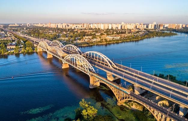 Vista aerea di un treno elettrico urbano di kiev che attraversa il dnieper dal ponte darnytsia. ucraina, europa orientale