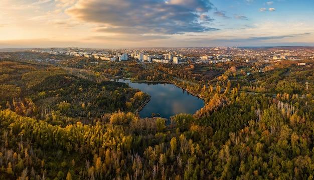 Vista aerea di un lago in un parco con alberi d'autunno. chisinau, moldavia. volo aereo epico sull'acqua. colorati alberi autunnali durante il giorno.