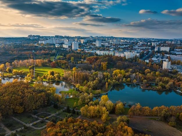 Vista aerea di un lago in un parco con alberi d'autunno. chisinau, moldavia. volo aereo epico sull'acqua. alberi autunnali colorati durante il giorno.