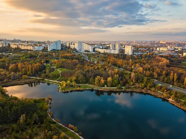 Vista aerea di un lago in un parco con alberi autunnali. chisinau, moldavia. volo aereo epico sull'acqua. alberi autunnali colorati durante il giorno.
