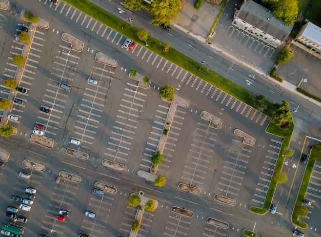 Vista aerea di un gran numero di auto di diverse marche in piedi parcheggio vicino al centro commerciale nel parcheggio diviso da strisce divisorie bianche e marciapiedi