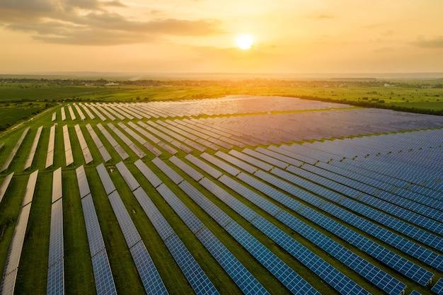 Vista aerea di una grande centrale elettrica sostenibile con molte file di pannelli fotovoltaici solari