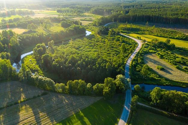 Vista aerea del paesaggio rurale lettone con un fiume tortuoso, foreste e strade di campagna al tramonto