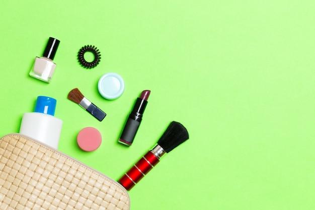 Vista aerea di una borsa per cosmetici in pelle con prodotti di bellezza per il trucco che si rovesciano su sfondo verde. bellissimo concetto di pelle con copia spazio.