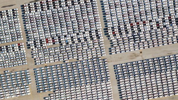 Vista aerea lotto di veicoli in parcheggio per auto nuove per esportazione, affari e logistica