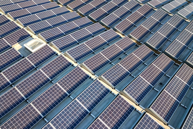 Vista aerea di molti pannelli solari fotovoltaici montati sul tetto di un edificio industriale.