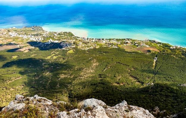 Vista aerea ipnotizzante vista della città di colline e foreste vicino al villaggio costiero e il mare blu in una soleggiata giornata estiva