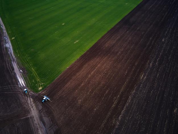 Vista aerea di un moderno trattore verde che ara il campo agricolo secco, preparando il terreno per la semina, la primavera, il video drone.