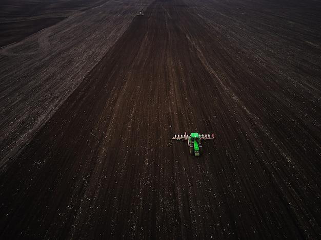 Vista aerea di un moderno trattore verde che semina campo agricolo, preparando il terreno per la semina, primavera, video drone.