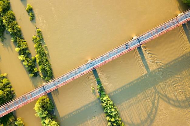 Vista aerea di uno stretto ponte stradale che si estende su un ampio fiume fangoso nella verde zona rurale