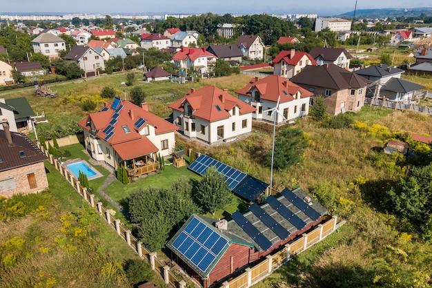 Vista aerea di una nuova casa autonoma con pannelli solari, termosifoni sul tetto, turbina eolica e cortile verde con piscina blu.