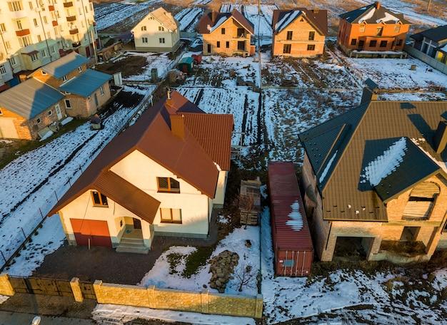 Vista aerea del nuovo cottage della casa residenziale e garage annesso con tetto in scandole sul cortile recintato in giornata invernale di sole nella moderna area suburbana. perfetto investimento in casa da sogno.
