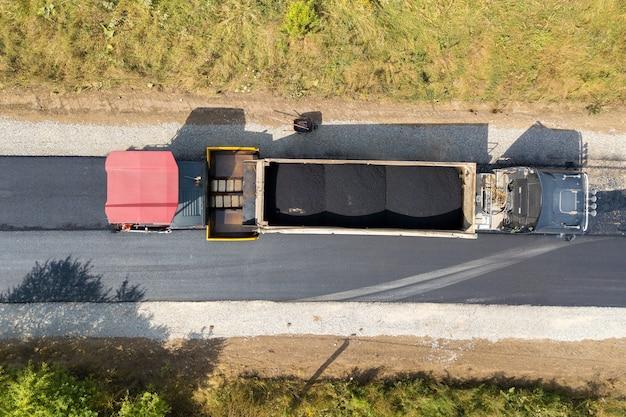 Vista aerea della nuova costruzione di strade con macchine per la posa di asfalto al lavoro.