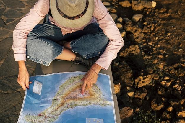 Sopra la vista aerea di una bella donna avventuriera che cerca sulla mappa la sua prossima fermata e la posizione del luogo di destinazione. turismo e modo alternativo di viaggiare e scoprire il mondo. voglia di viaggiare e vita felice