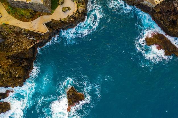 Vista aerea delle scogliere dell'isola dell'oceano con enormi onde bianche e acqua cristallina