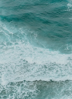 Vista aerea dell'oceano con le onde e le rocce durante una giornata luminosa, rilassante scena sui toni del blu
