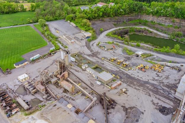 Vista aerea della cava panoramica di miniere a cielo aperto con molti macchinari in attrezzature di lavoro in un impianto