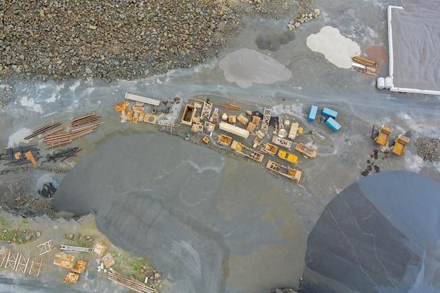 Vista aerea della cava panoramica di miniere a cielo aperto con un sacco di macchine al lavoro in una cava