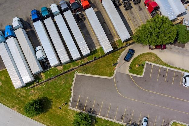 Vista aerea del parcheggio con camion sul trasporto del bacino di logistica dei rimorchi dell'area di sosta del camion