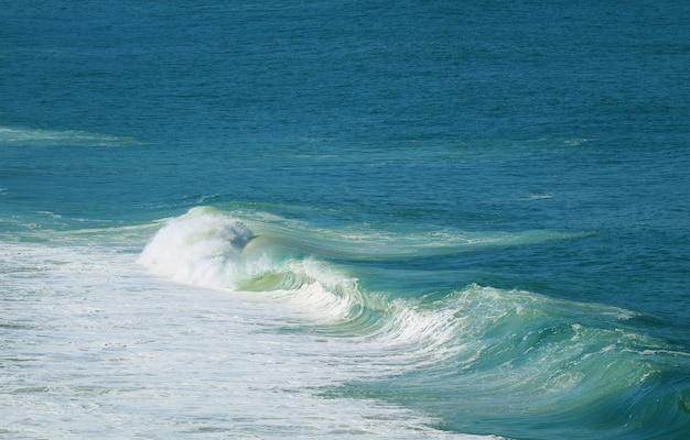 Vista aerea di potenti onde che schizzano sul vibrante mare blu