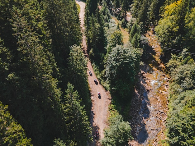 Vista aerea dei motociclisti del quad allo spazio della copia della strada del sentiero di montagna