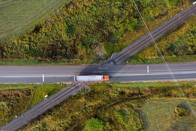 Vista aerea dei binari della ferrovia che attraversano una strada asfaltata con auto in zona rurale