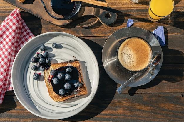 Vista aerea di un ricco toast di pane con mirtilli freschi e marmellata di mirtilli che accompagna un caffè nero.