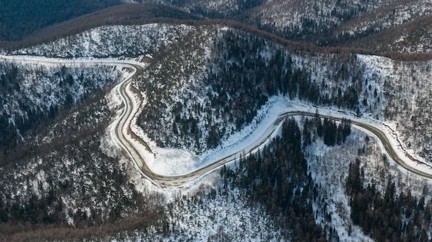 Vista aerea del fiume e foreste della taiga e strada nel paesaggio astratto primavera inverno della natura settentrionale con drone