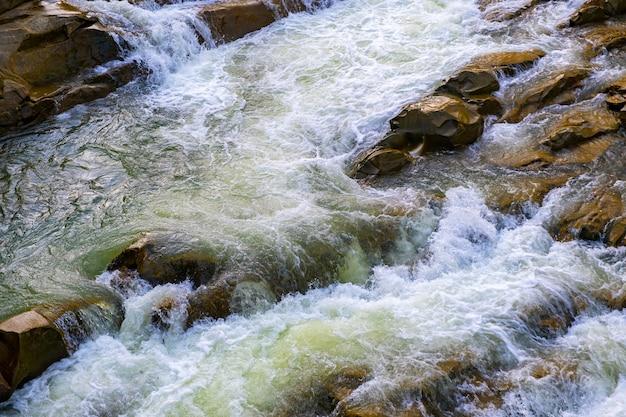 Vista aerea della cascata del fiume con acqua turchese chiara che cade tra massi bagnati con spessa schiuma bianca.