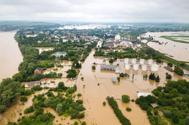 Vista aerea di un fiume con acqua sporca e case allagate