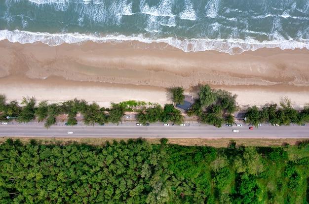 Vista aerea della strada tra l'albero e il grande oceano di giorno in thailandia