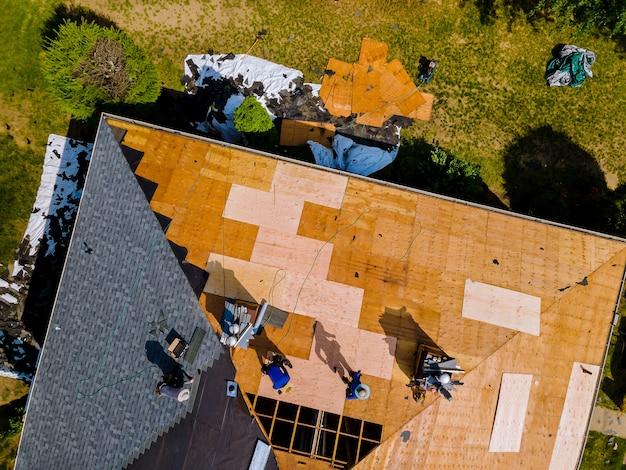 Vista aerea del riparatore della costruzione del tetto su un appartamento residenziale con il nuovo tetto
