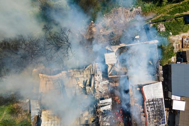 Vista aerea di un edificio in rovina in fiamme con tetto crollato e fumo scuro in aumento.