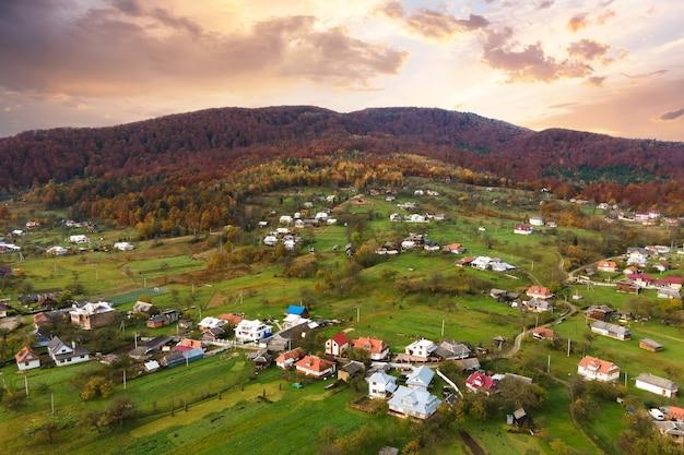 Vista aerea di un villaggio rurale con piccole case tra colline di montagna autunnali ricoperte di pini gialli e verdi.