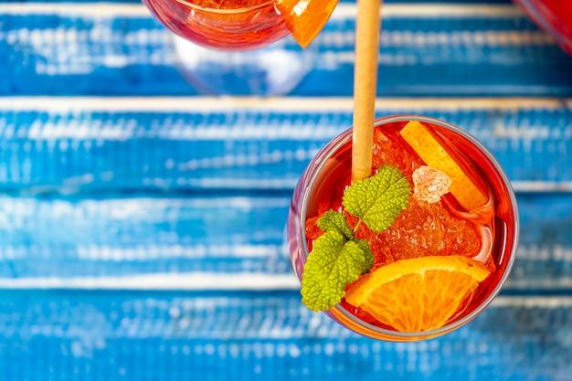 Vista aerea di un tavolo blu rustico con un bicchiere del rinfrescante cocktail aperol spritz